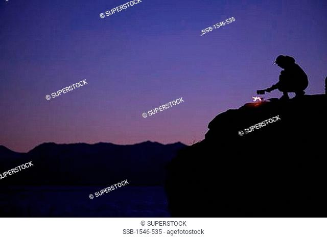 Silhouette of a person cooking over fire on a rock