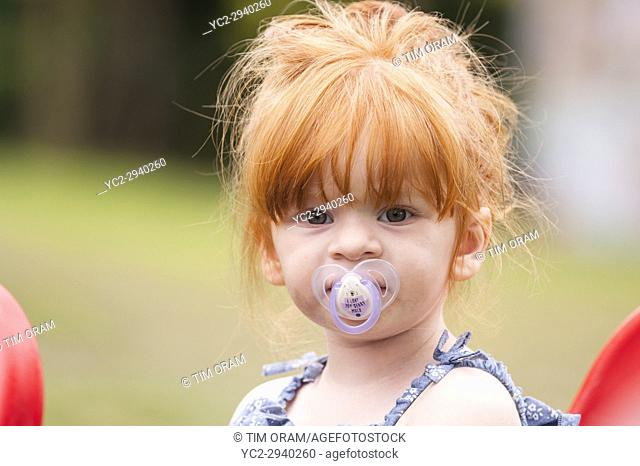 A 2 year old girl with a dummy outdoors in the Uk