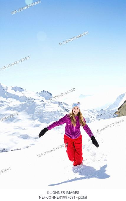 Young woman running through snow