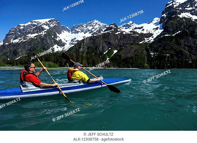 Two middle-aged men kayak in Thumb Cove with Spruce Glacier hanging in the background, Thumb Cove State Marine Park, Kenai Peninsula, Southcentral Alaska, USA