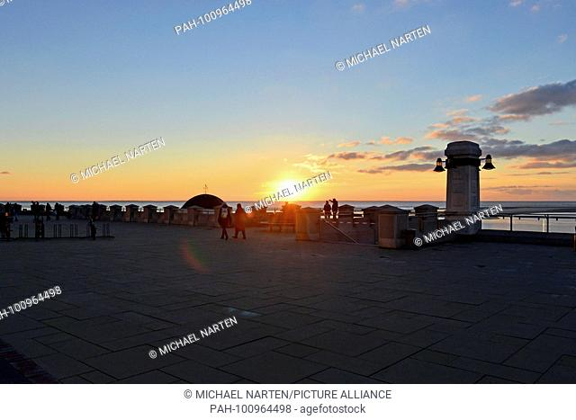 Borkum's upper seafront promenade with beams of the setting sun above the ocean, 11 November 2016 | usage worldwide. - Borkum/Niedersachsen/Germany