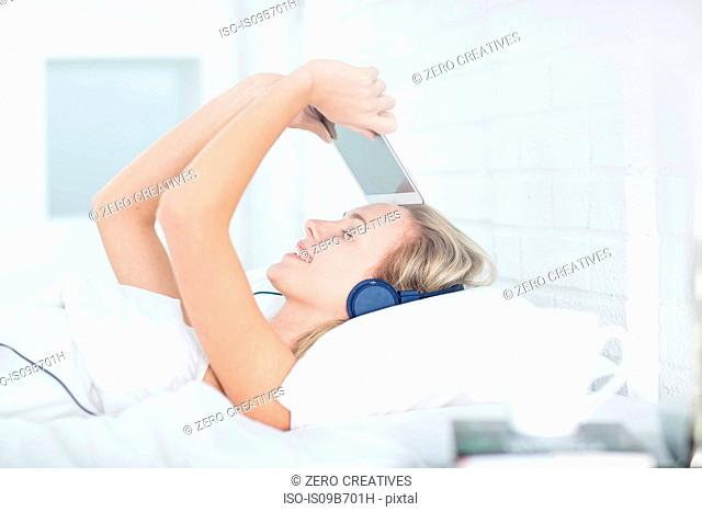Young woman lying in bed, wearing headphones, holding digital tablet