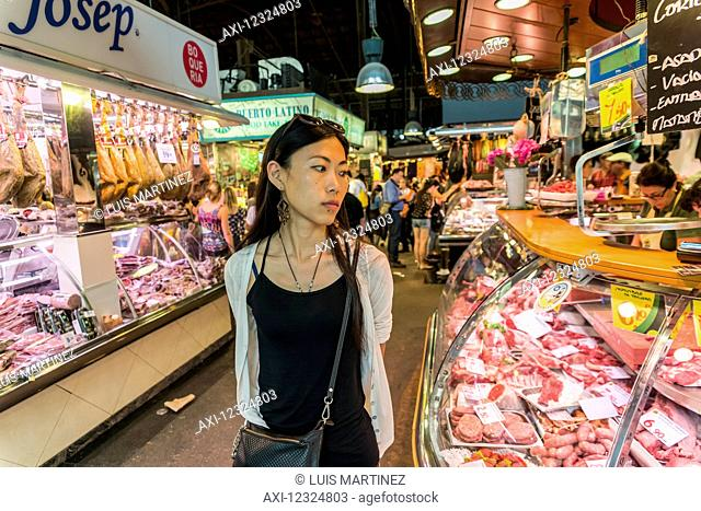 A young Chinese woman shops at Boqueria Market, one of the most famous markets around Spain and the most famous in Barcelona; Barcelona, Catalonia, Spain
