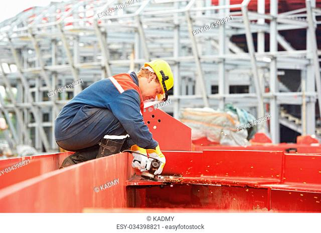 builder worker in safety protective equipment smothing out welded joint at metal construction frame by grinding machine
