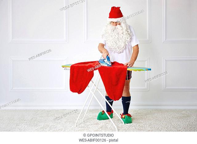 Santa claus ironing his pants