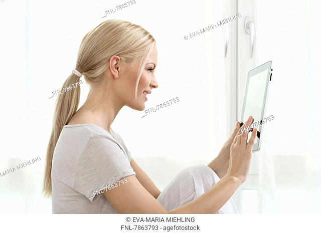 Young blond woman using tablet PC at home