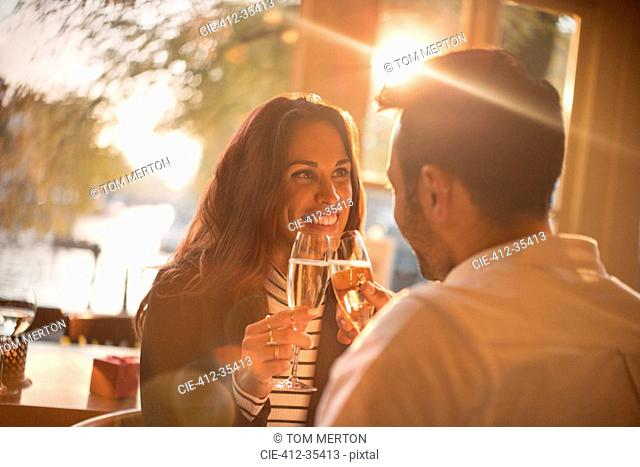 Affectionate young couple toasting champagne glasses in restaurant