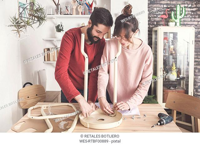 Young couple assembling flat-pack stool at home