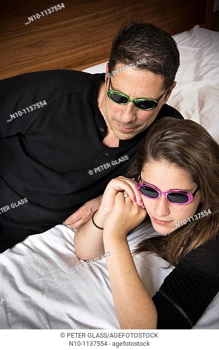 Teen girl and her father, both wearing sunglasses