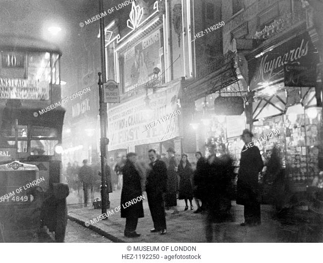 Crowds outside a cinema, London, c1930s. People on the street at night, some waiting at a bus stop. The route of the number 10 bus is via Walworth Road in...