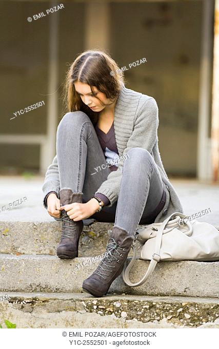 Teenager girl is tying boots