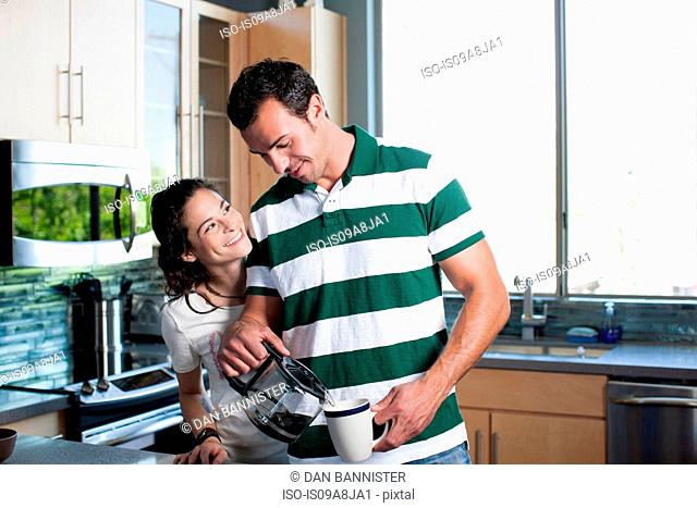 Young couple pouring coffee from pot in kitchen, smiling