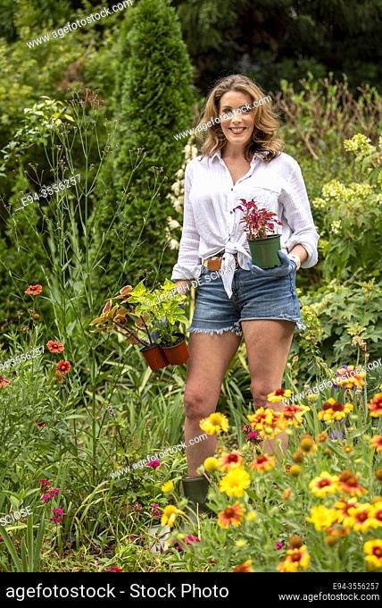 A pretty 37 year old redheaded woman in a garden setting surrounded by annual and perennial plants in the early summer