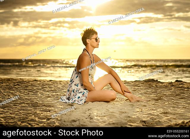 beautiful woman in a long dress sitting on the sand at the beach at sunset