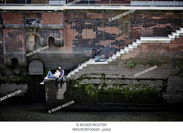 Germany, Hamburg, couple with electric bicycle relaxing at Old Warehouse District