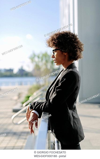 USA, New York City, profile of businesswoman leaning on railing