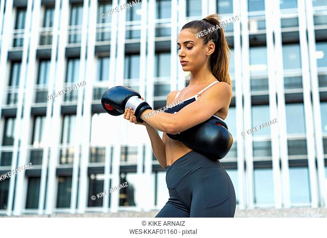 Sportive young woman putting on boxing gloves in the city