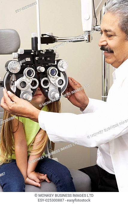 Optician In Surgery Giving Girl Eye Test