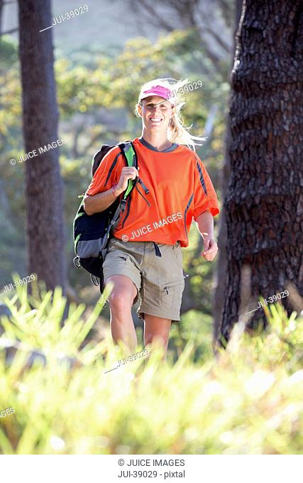 Portrait of smiling woman hiking with backpack in woods