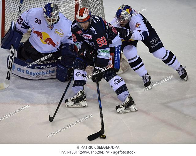 Schwenningen's Istvan Bartalis (C) and Munich's Aucoin Keith (R) vie for the puck during the Germany DEL ice hockey match between Schwenninger Wild Wings and...