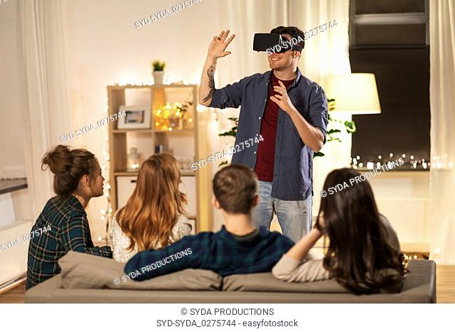 man in vr glasses at home with friends