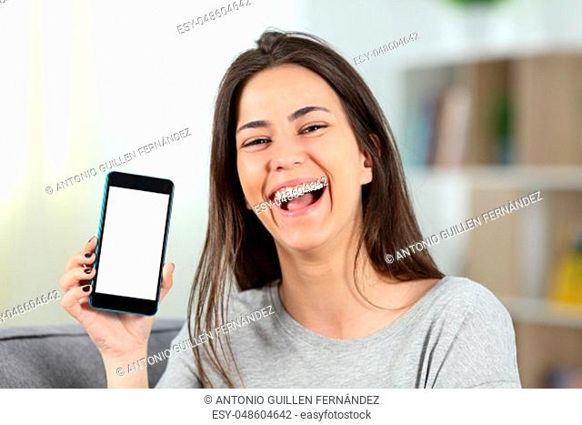 Joyful teen showing a mockup phone screen to camera sitting on a couch in the living room at home