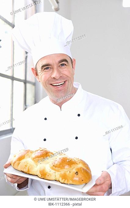 Confectioner holding a braided yeast bun