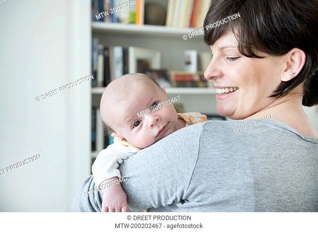Mother holding her baby, smiling