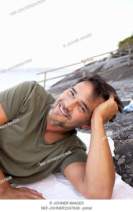 Smiling man relaxing on beach