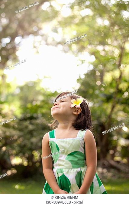 Young girl in garden, wearing flower in her hair