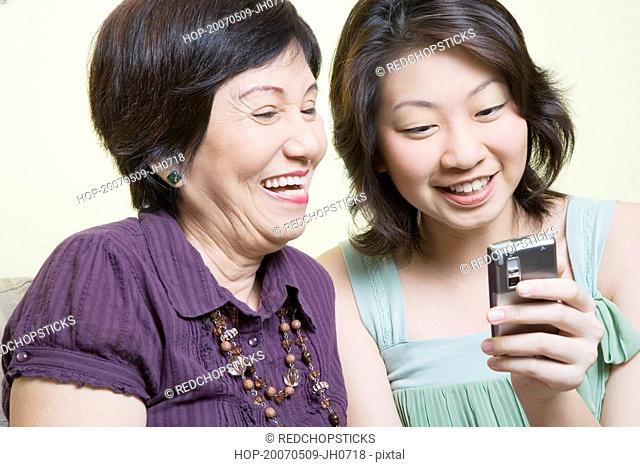 Close-up of a senior woman and her granddaughter looking at a mobile phone and smiling
