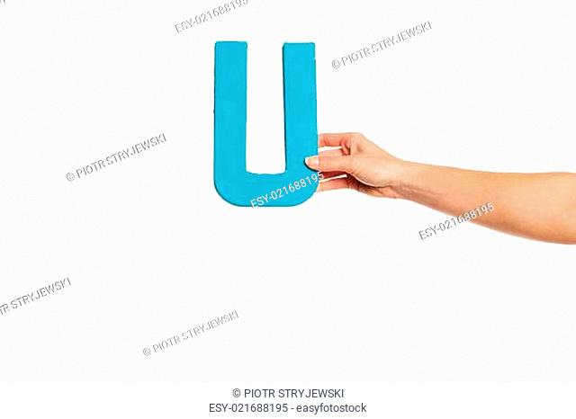 hand holding up the letter U from the right