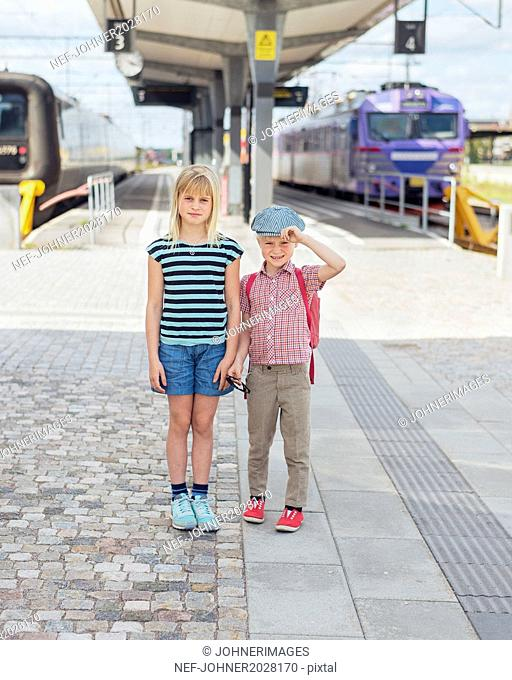 Brother and sister on train station