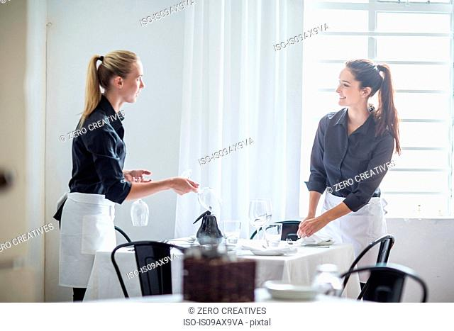 Waitresses chatting and setting table in restaurant