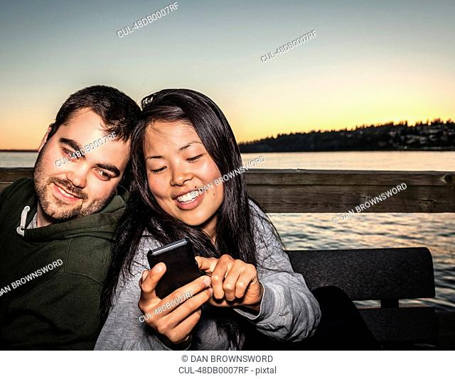 Couple using cell phone outdoors