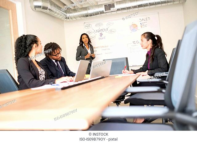 Businessman and businesswomen in meeting room, businesswoman, standing at front, explaining business strategy