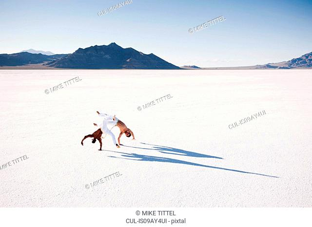 Elevated view of two men performing capoeira on Bonneville Salt Flats, Utah, USA
