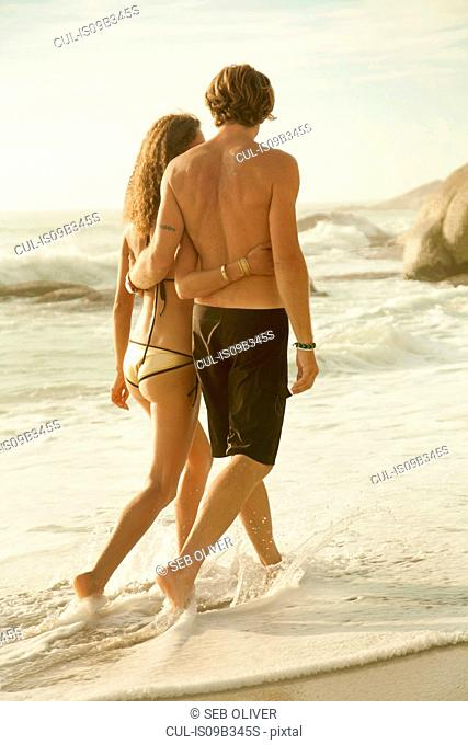 Couple walking along beach, rear view