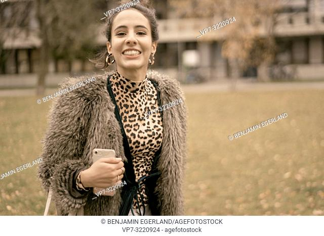 fashionable lively woman walking outdoors in park, autumn season, wearing coat, happy, candid emotion, unposed walking in city, Munich, Germany