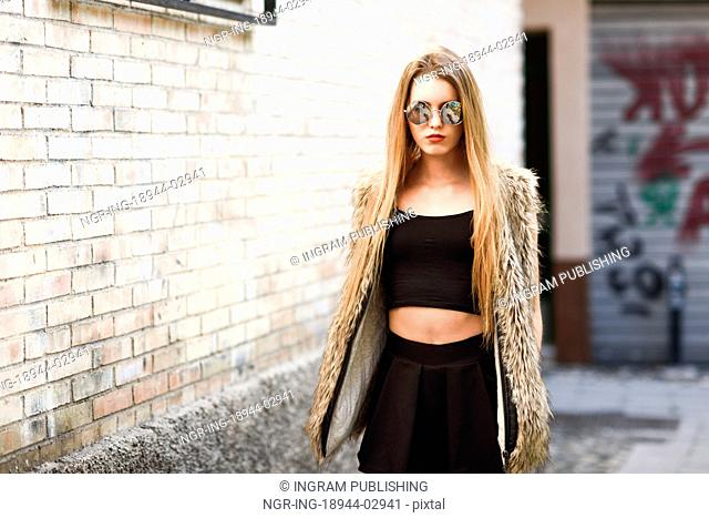 Portrait of blonde girl in urban background wearing round sunglasses
