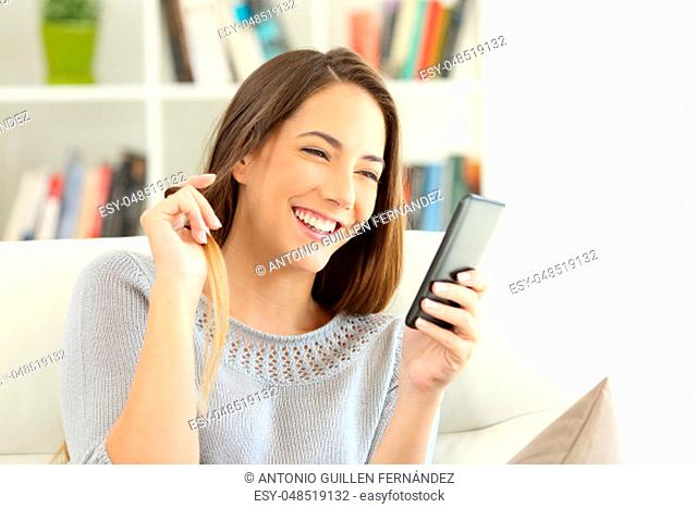 Girl flirting on line with a smart phone sitting on a couch in the living room at home