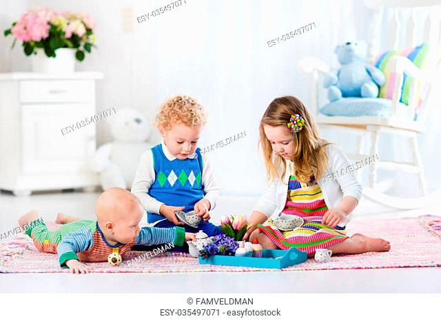 Kids play at home. Children playing in white sunny nursery. Little girl having fun at doll tea party with her brothers. Siblings making lunch for toy bear