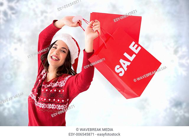 Composite image of pretty brunette showing sale bag and shopping bag