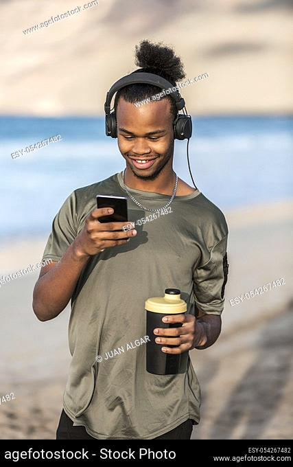 Cheerful African American guy holding cup of hot drink and listening to music while standing near sea and using smartphone
