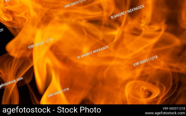 Thin trickle of fiery orange-red smoke slowly rising graceful twists up on black background. Colored smoke blowing from bottom to top. Closeup