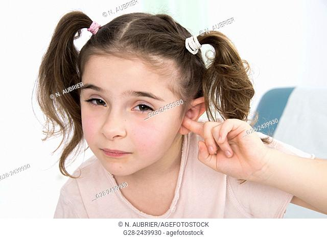 Little girl with bunches stopping her ear with her finger sitting on a medical couch