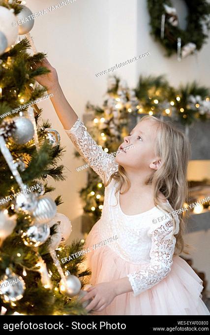 Portrait of blond little girl decorating Christmas tree