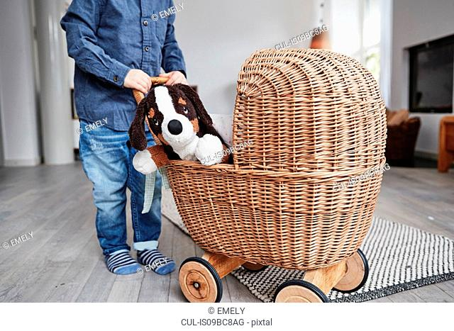 Young boy pushing wicker dolls pram, toy dog sitting in pram, low section