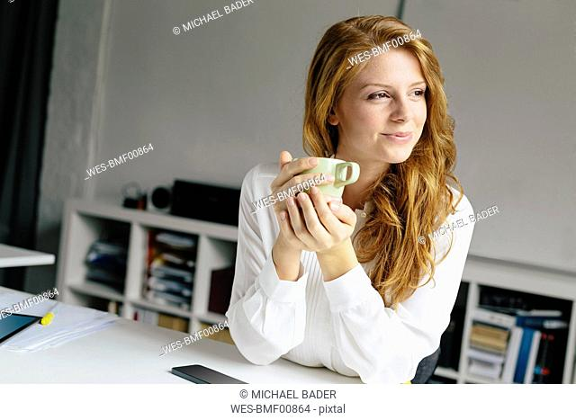 Smiling young woman with cup of coffee at desk in office