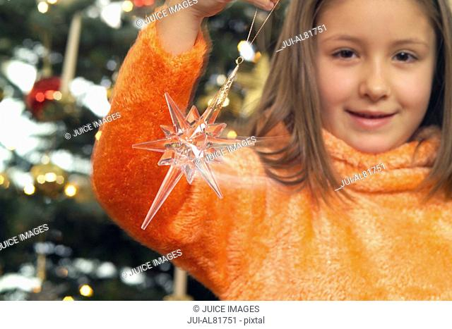 Girl holding star Christmas ornament